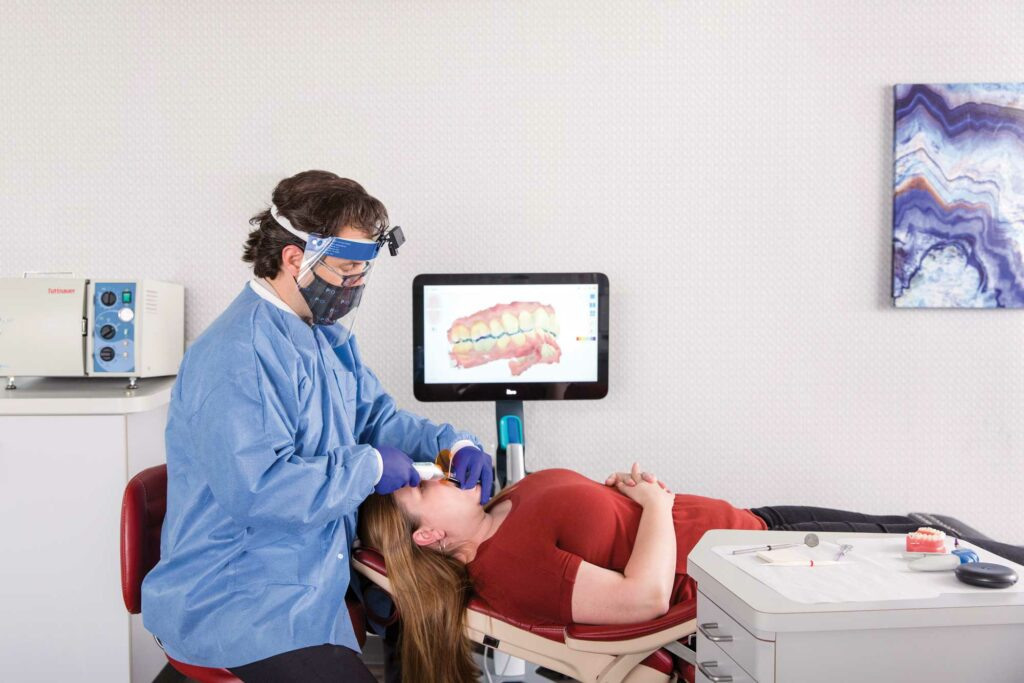 Dr Jonathan Nicozisis scanning a patient's teeth